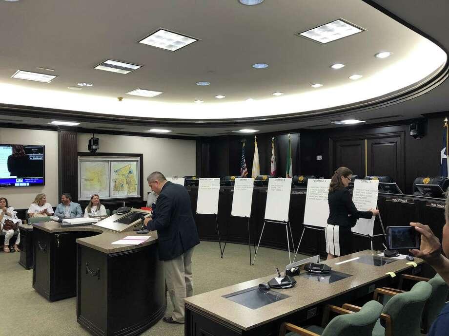 Funcionarios colocan los nombres de los candidatos en las carteleras de cada distrito el martes en el ayuntamiento municipal. Photo: Julia Wallace /Laredo Morning Times