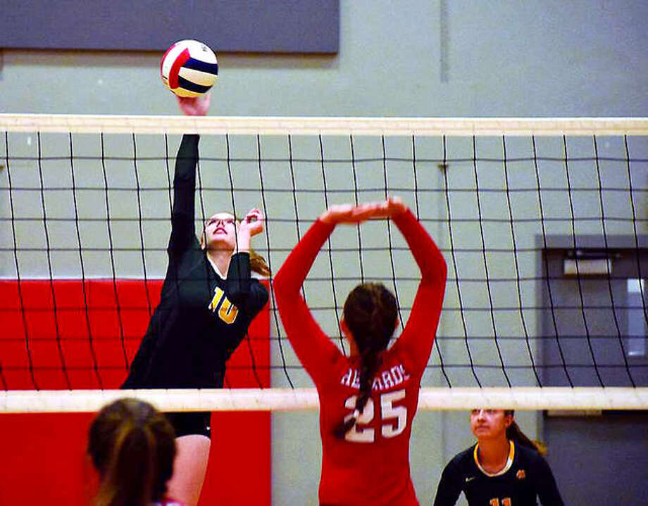 Metro-East Lutheran's Taylor Bradley goes up for the ball Wednesday night against Alton as the Redbirds' Brooke Wolff (25) defends. Photo: Matthew Kamp | For The Telegraph