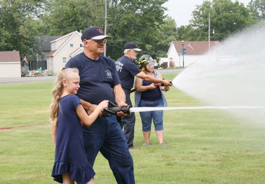 A big part of the fun witnessed at Port Hope's annual ABC Day was at the fire hall as kids and adults played games, received souvenirs and took tours of the station. Pictured is Port Hope Fire Chief Gary Schave helping a youngster as she learns to handle a real fire hose. Photo: Rich Harp/For The Tribune