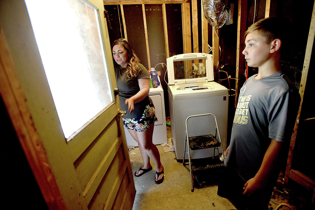 Amanda Allison shows the damage and disrepair their home remains in after taking on 6 1/2 feet of flood water during Tropical Storm Harvey as son Tanner, 11, looks on. The Allison family were flooded out of their home on Third Street in Vidor along with neighbors throughout the area. Recovery has been slow, and the family of 5 are still living in trailers set up in the back yard. Many of the rooms in the house now serve as storage for recovered items or places to hang clothes. Wednesday, August 22, 2018 Kim Brent/The Enterprise