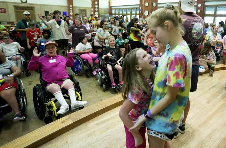 Rebecca Lowery, left, dances with her counselor, Maddie Farrell, during Camp Smiles at Camp For All in Burton, Texas.