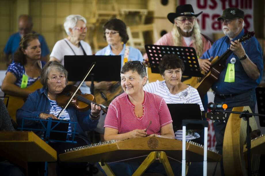 Joann Satkowiak of Linwood, center, leads a group of musicians in a jam session during the Midland Folk Music Festival on Thursday, Aug. 23, 2018 at the Midland County Fairgrounds. The festival features concerts and workshops and continues through Sunday. For more photos, go to www.ourmidland.com. (Katy Kildee/kkildee@mdn.net) Photo: (Katy Kildee/kkildee@mdn.net)