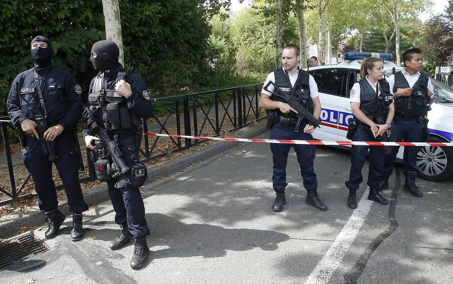 Hooded police officers guard a street with other officers after a knife attack in Trappes, west of Paris. A suspected radical killed his mother and sister and seriously injured another woman. Photo: Michel Euler / Associated Press