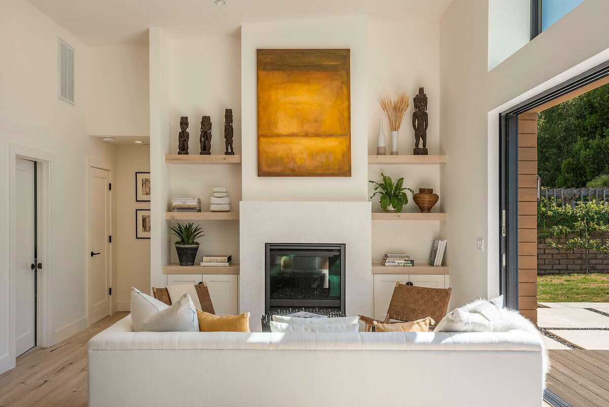 Display shelves and custom built-ins surround the great room?'s gas fireplace.