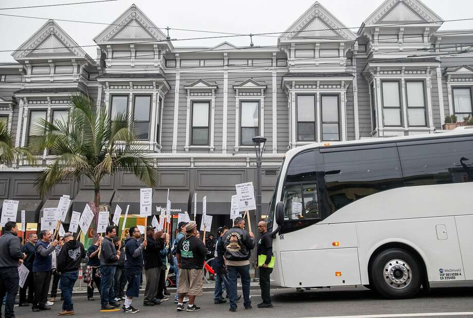Members of the Teamsters Union carry signs as they block a shuttle bus at 18th and Castro streets in San Francisco. Photo: Photos By Jessica Christian / The Chronicle
