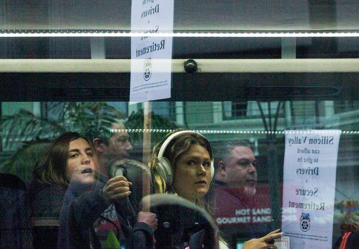 A tech worker looks out the window as Teamsters Local Union members gather at 18th and Castro streets to protest working conditions of corporate shuttle bus drivers in San Francisco, Calif. Thursday, Aug. 23, 2018