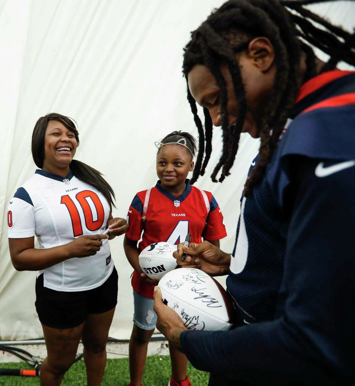 Hurricane Harvey flood victim Eraina Garrett, left,, and Mya Wagner smile as they meet Houston Texans wide receiver DeAndre Hopkins (10) as Texans players welcomed Harvey victims to training camp at the Methodist Training Center on Thursday, Aug. 23, 2018, in Houston.