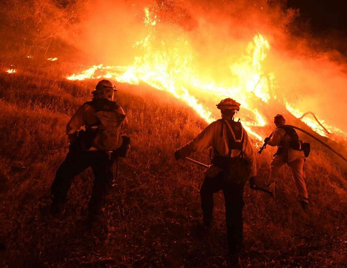 Firefighters conduct a controlled burn to defend houses against flames from the Ranch Fire, part of the Mendocino Complex Fire.