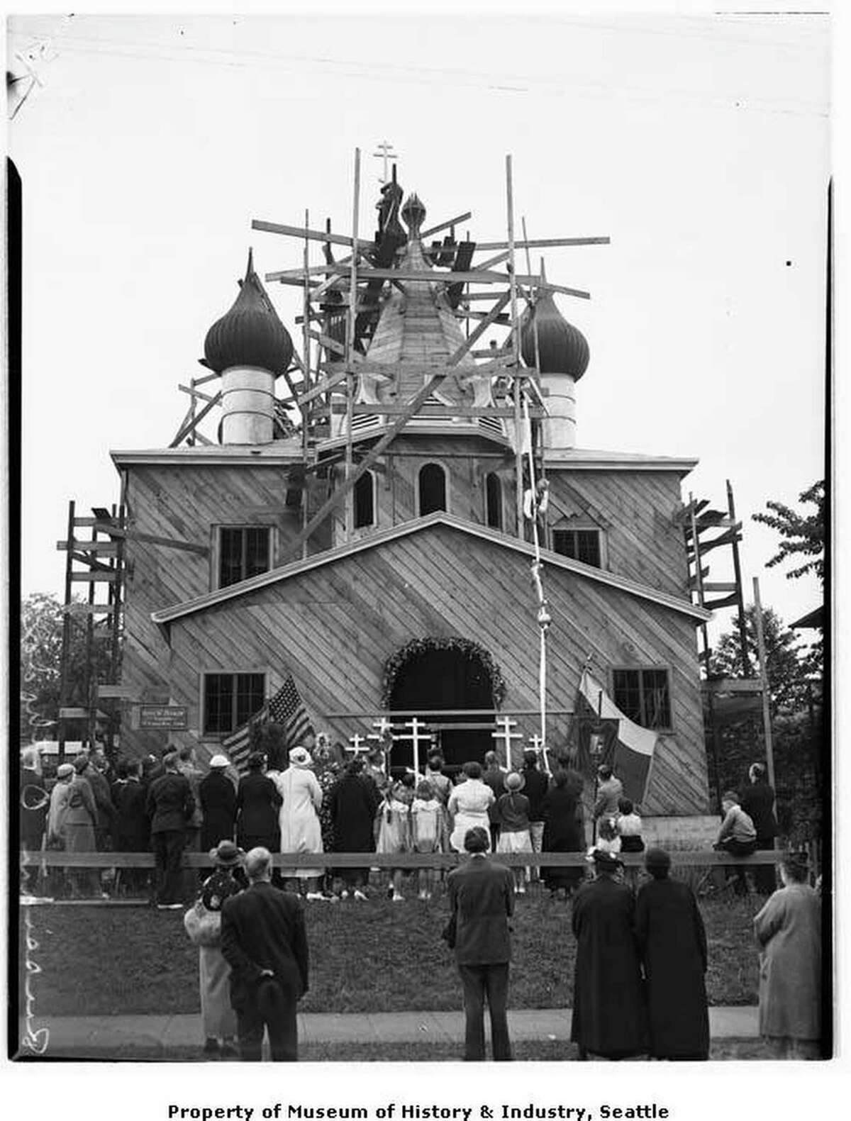 St. Nicholas Russian Orthodox church during construction, Seattle, 1937. St. Nicholas Russian Orthodox Church is located at 1714 13th Avenue East in Seattle's Capitol Hill neighborhood. It features the onion domes common to Russian church architecture. One of the oldest Russian Orthodox parishes in the U.S., it was founded in 1932 by Russian immigrants. The church building shown here was consecrated in December 1937 and dedicated to the 4th century Greek saint, Nikolaos of Myra. Here a crowd watches the cross being raised to the top of the building. (Courtesy of MOHAI)