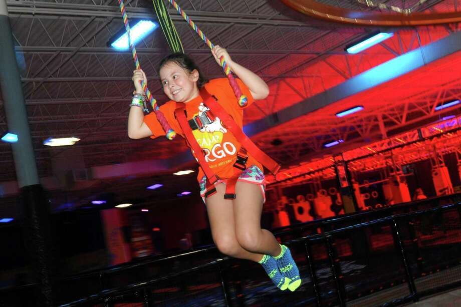 Maggie Nevis, of Orange, swings while riding down a zip line at the Urban Air Trampoline & Amusement Park, in Orange, Conn. Aug. 23, 2018. Photo: Ned Gerard / Hearst Connecticut Media / Connecticut Post