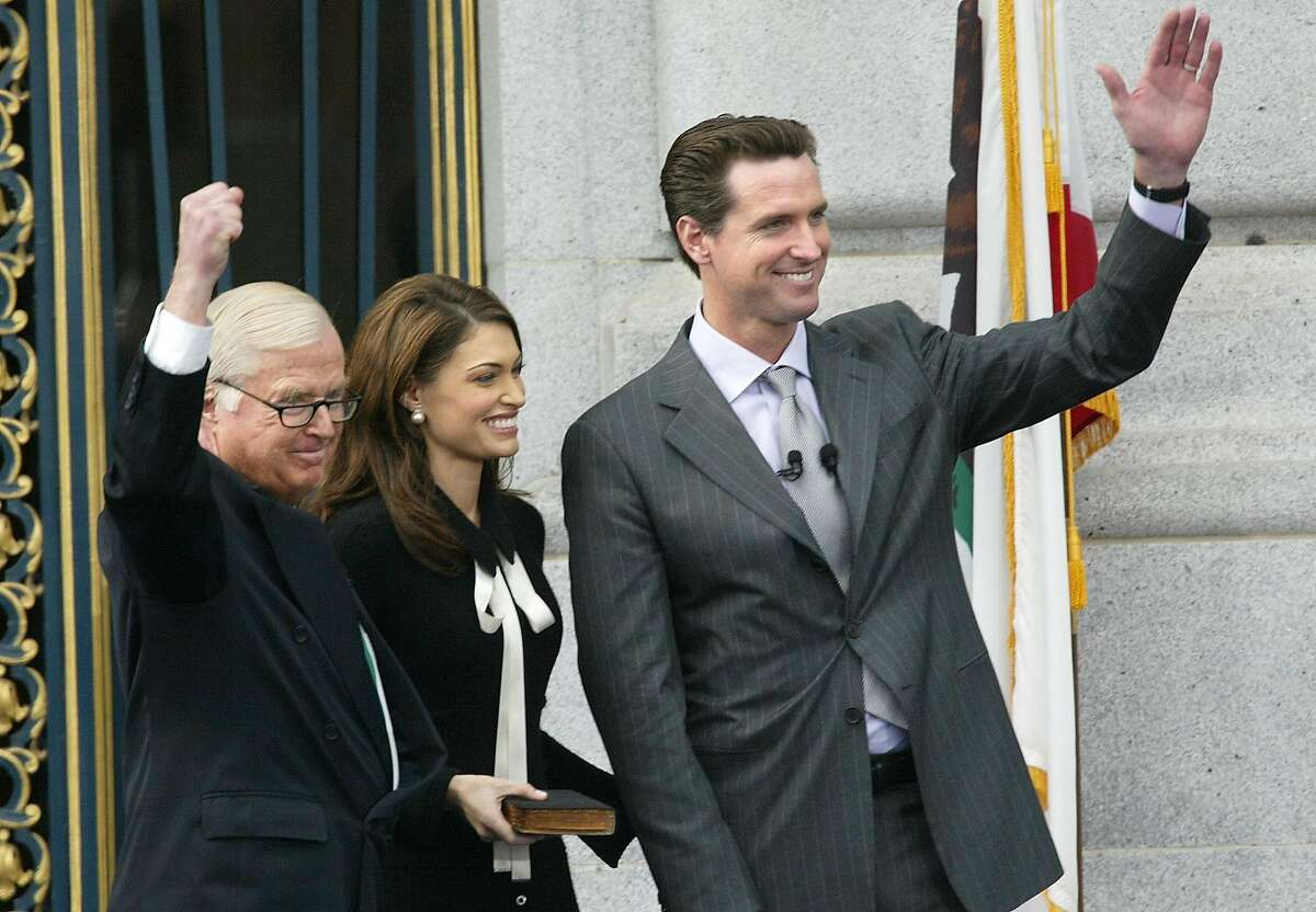 Newly sworn-in San Francisco Mayor Gavin Christopher Newsom, right, waves to supporters after taking the oath of office from his father, Judge William Newsom, left, on Thursday, Jan. 8, 2004, at City Hall in San Francisco. At center is Kimberly Guilfoyle Newsom, the mayor's wife. (AP Photo/Jeff Chiu)