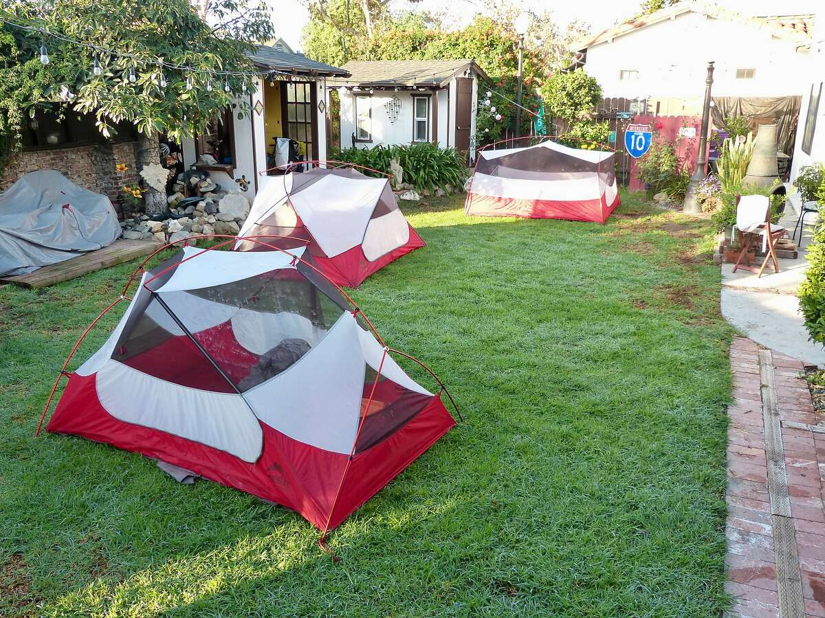 Bicyclists pitch tents in the yard of a host.