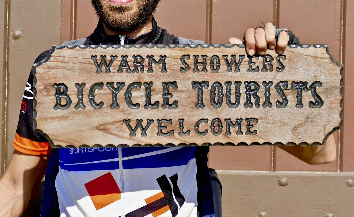 A bicyclist holds up the WarmShowers.org Welcome sign.