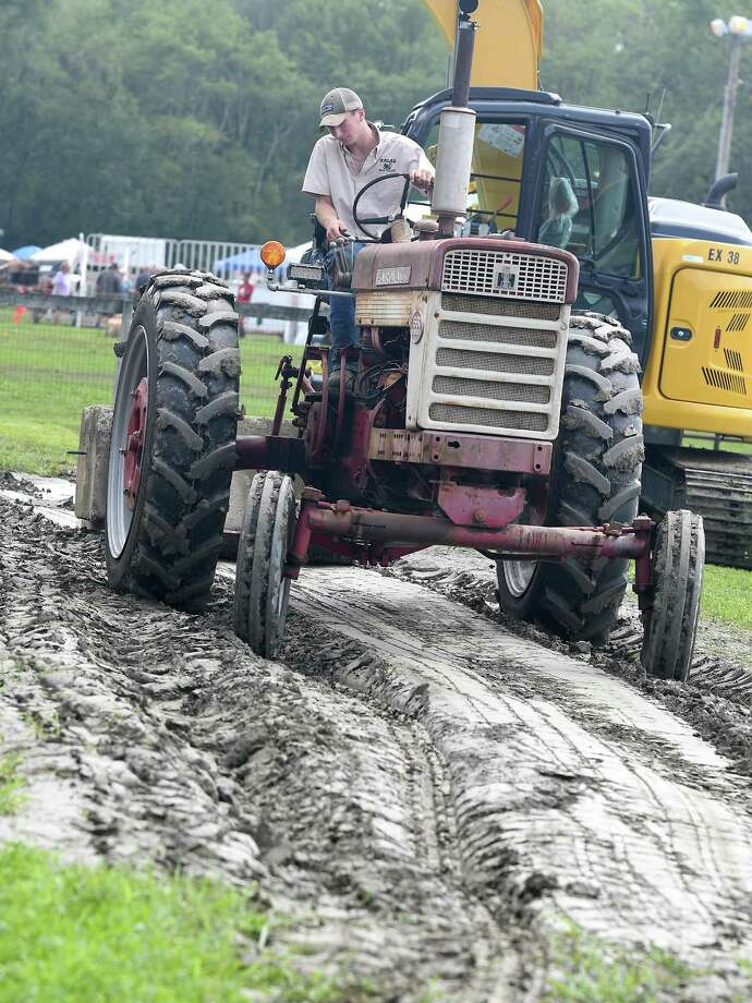 Bradley Potpan, 18, of Danbury, deals with muddy conditions which eventually cancelled the tractor pull competition at the Bridgewater Country Fair in Bridgewater on Saturday. Photo: Krista Benson / / The News-Times Freelance