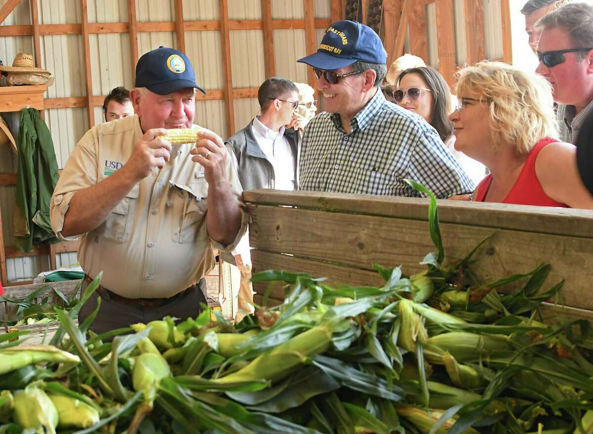 U.S. Secretary of Agriculture Sonny Perdue, left, and Congressman John Faso, center, take a tour of the Altobelli Family Farm on Thursday, Aug. 23, 2018 in Valatie, N.Y. Farm owner Becky Altobelli, right, watches as Perdue tries their corn. (Lori Van Buren/Times Union)