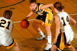 Dow High's Jillian MacDonald looks for a driving lane during a district tournament game against Cadillac in 19999.