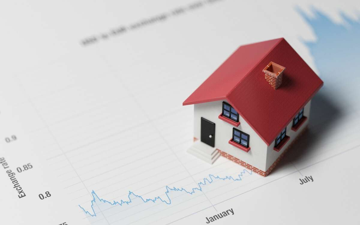 High quality 3d render of a miniature house on a blue financial chart. Housing market concept. Miniature house is lit by the upper left corner of composition. Horizontal composition with copy space. Great use for real estate and morgage related concepts.