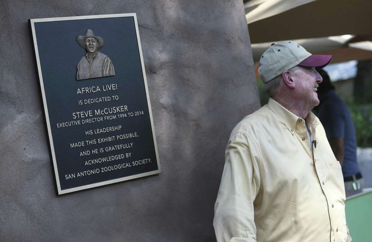 Steve McCusker stands next to a plaque dedicating the Africa Live! exhibit at the San Antonio Zoo to him.