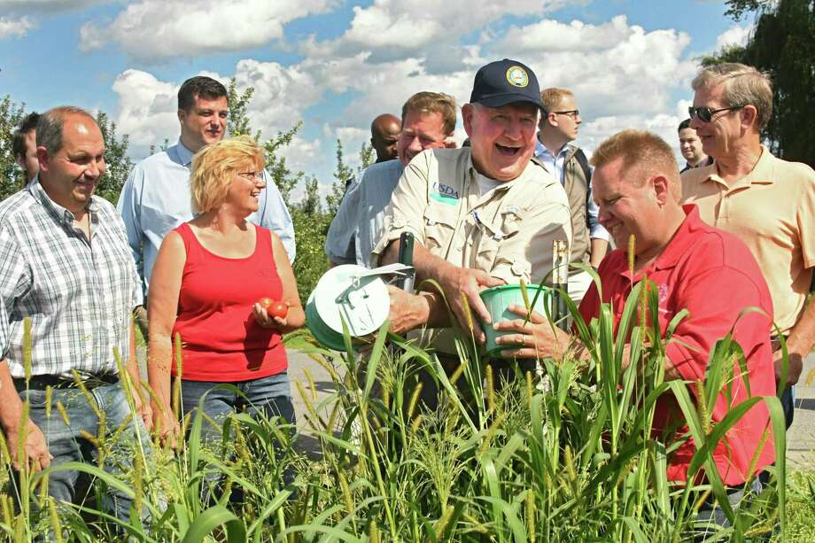 U.S. Secretary of Agriculture Sonny Perdue laughs as Chuck Bornt of Cornell Cooperative Extension, right, shows him an insect monitor device as he takes a tour of the Altobelli Family Farm on Thursday, Aug. 23, 2018 in Valatie, N.Y. Farm owners John Altobelli and his wife Becky, left, show them around. (Lori Van Buren/Times Union) Photo: Lori Van Buren / 20044633A
