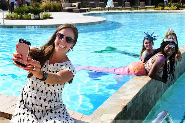 Suzanne Johnson, of SugarLand, poses for a selfie with a trio of Houston Mermaids during the grand opening of the Crystal Lagoon in the Balmoral community in Humble on August 23, 2018.