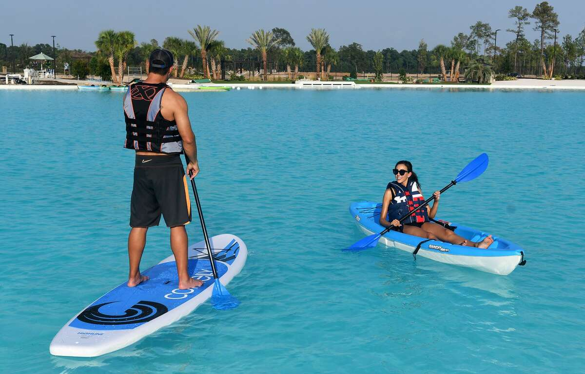 Ally Brown, right, of Katy, and Carlos Sepulveda, left, both actors with Pastorini-Bosby Talent Agency of Houston, work their kayak stand-up paddle board on the water during the grand opening of the Crystal Lagoon in the Balmoral community in Humble on August 23, 2018.