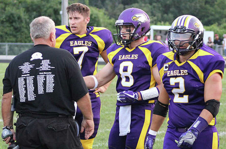 CM alumni Tory Doerr (7), A.J. Erzen (8) and Madi Mikhayel (2) meet with coach Rich Reinhart during a timeout at the CM vs. Jersey alumni game Saturday night at Hauser Field in Bethalto. The former Eagles relinquish the field to the newest edition of CM football on Friday night when the Eagles open the 2018 season at home against Marquette Catholic. Photo: Greg Shashack / The Telegraph