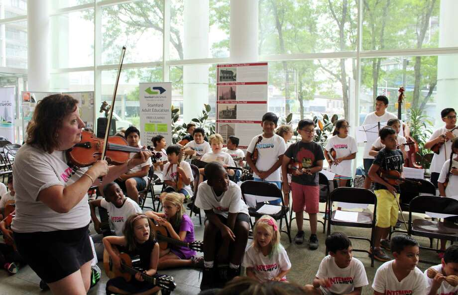 "An instructor with INTEMPO Summer Music Camp leads students in a performance of ""Vivir Mi Vida"" in Government Center last week. Photo: Erin Kayata / Hearst Connecticut Media / Stamford Advocate"