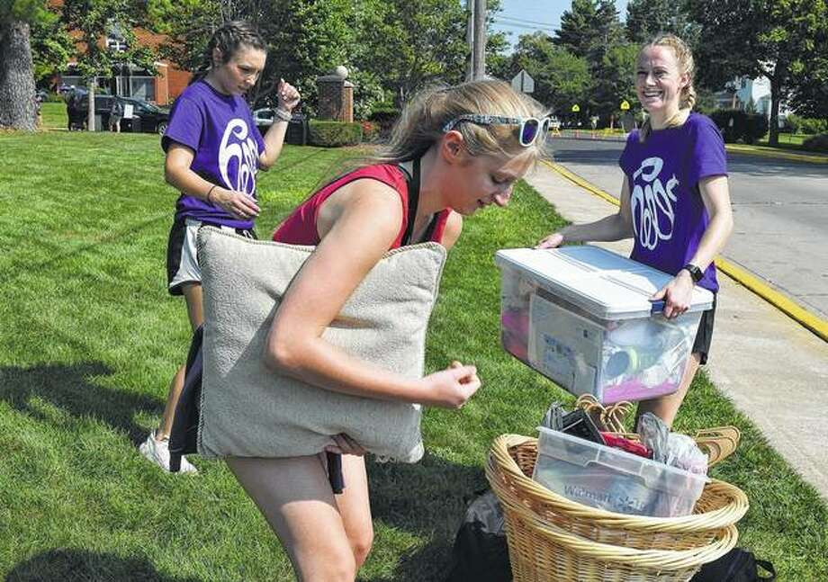 Illinois College freshman Mary Pruett (center) adjusts some of her belongings to carry Thursday as she moves into her residence hall. Photo: Samantha McDaniel-Ogletree | Journal-Courier