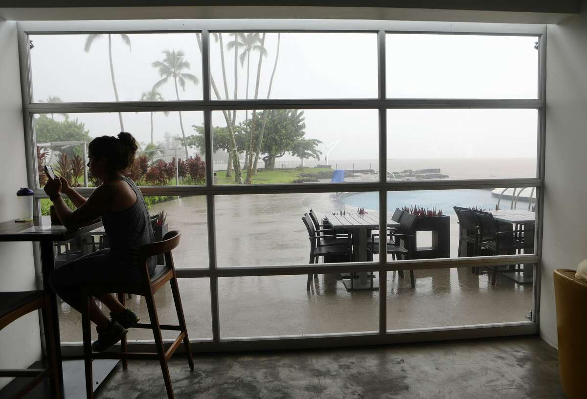 A woman sits in a hotel restaurant as rain falls on the Big Island on August 23, 2018 in Hilo, Hawaii. Hurricane Lane has brought more than a foot of rain to some parts of the Big Island which is under a flash flood warning.