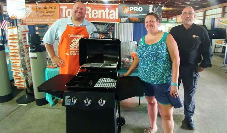 Cassie Schultz of Bay City is pictured with Mike Zielinski and Alan Osburn from the Midland Home Depot next to the brand new DynaGrill she won in the Home Depot Garden Club Drawing at the 2018 Midland County Fair. For the past five years, Home Depot has given away a grill to a lucky winner at the fair. It expects to be back again in 2019. (Photo provided)