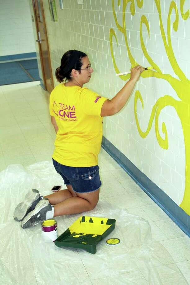 Local parent Melissa Checkley works on a tree mural at the Bad Axe Middle School, Monday morning. Volunteers showed up to help paint several walls at the school, which will be used by students to show off various projects throughout the year. (Seth Stapleton/Huron Daily Tribune)