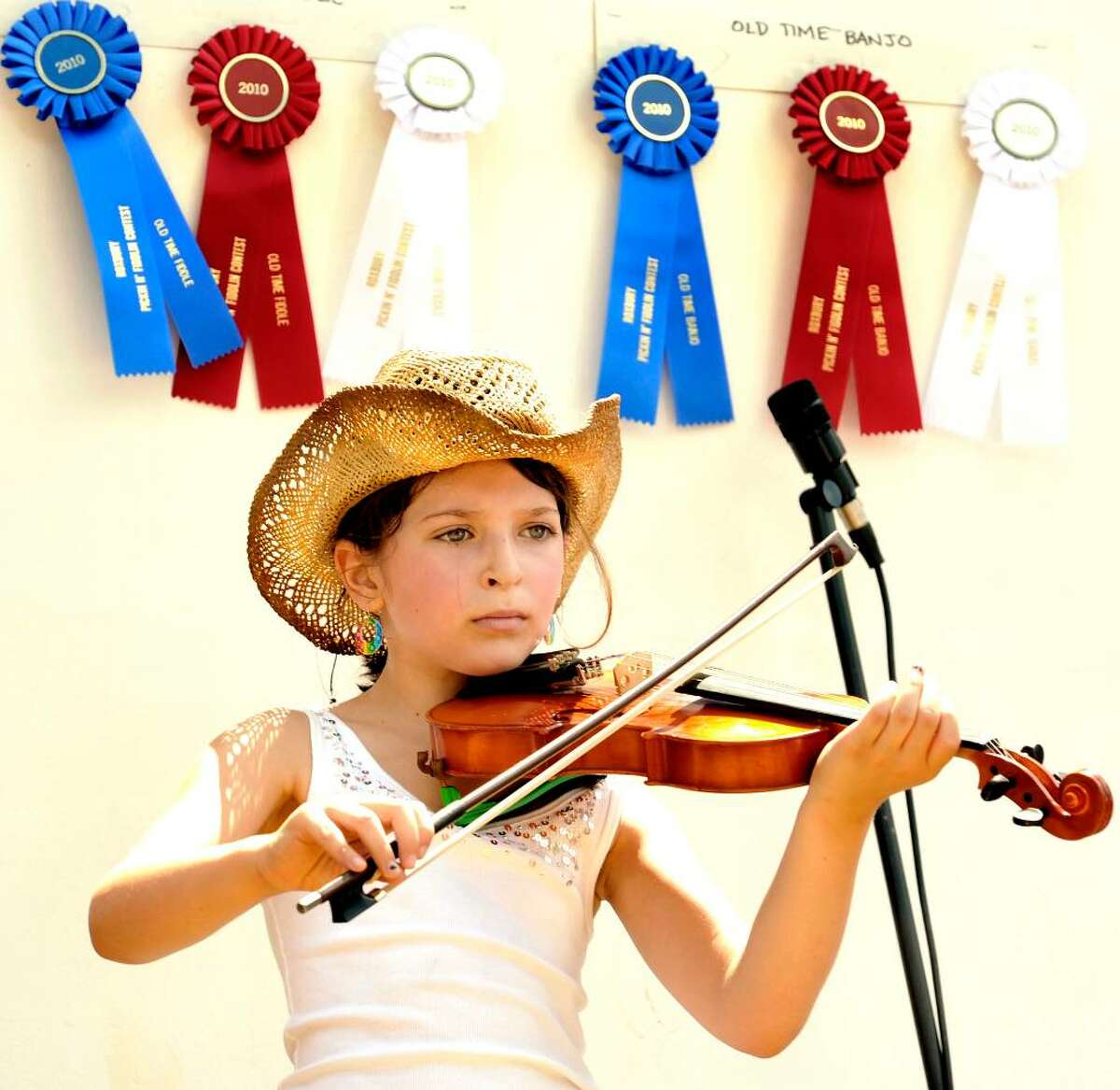 Jenna Hutensky, 8, of West Hartford, performs on stage during Pickin and Fiddlin, in Roxbury, on Sunday, July 11, 2010.