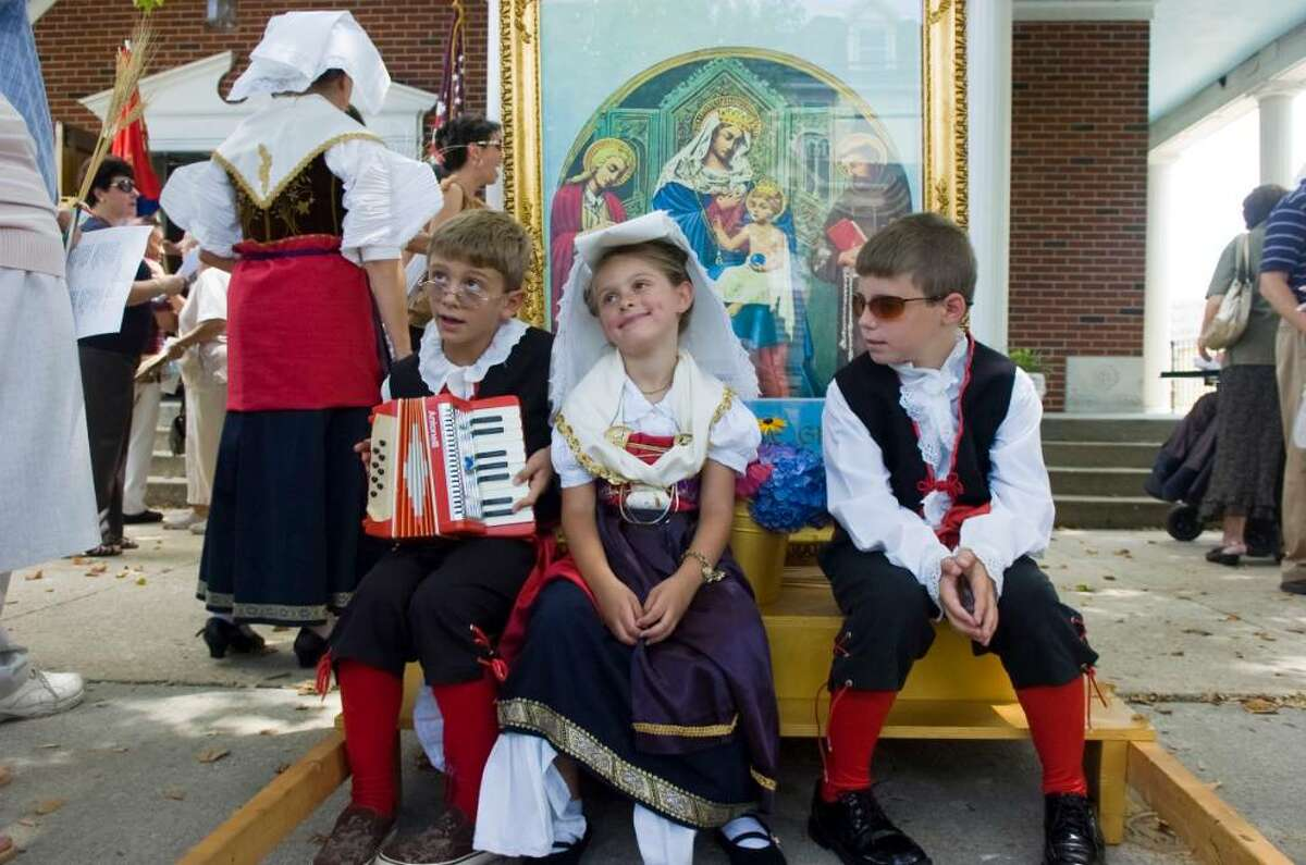 Nicky, 9, left, and Ariana Corrente, 6, and Nicky Palumbo, 7, relax after marching in the Minturnese Club's annual Festa de la Regne or