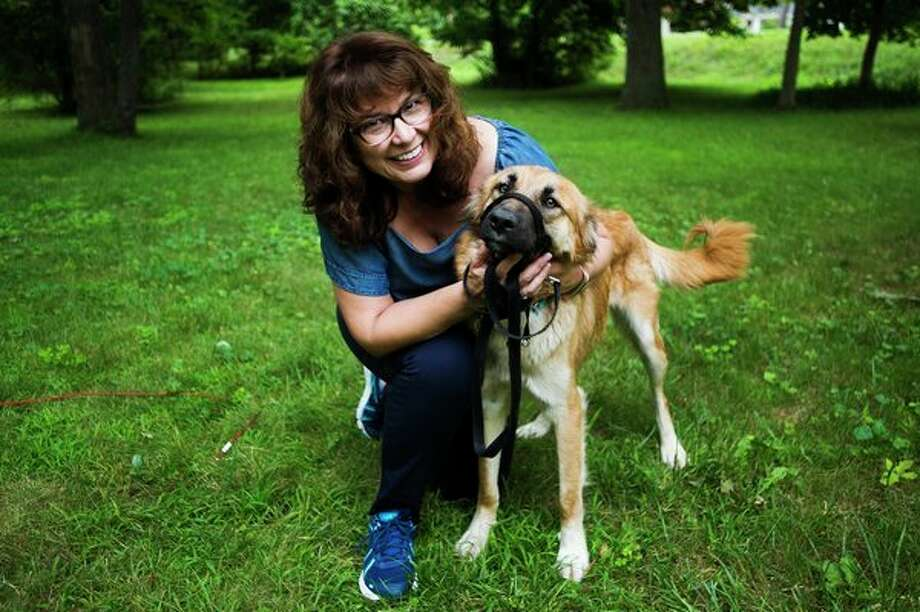 Trish Breen poses for a photo with Lucy, a dog that was rescued by her son, Senior Airman Christopher Williams, an aerial transportation specialist with the U.S. Air Force., during his deployment overseas. (Katy Kildee/kkildee@mdn.net)