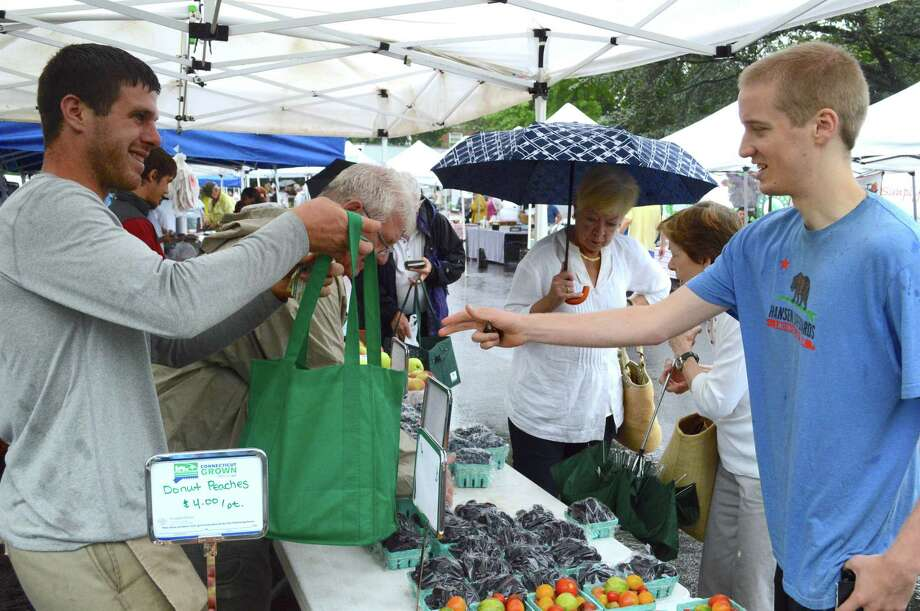 Regular Jimmy Baker of Darien makes his weekly berry purchase from Jesse Teveris of Woodland Farm of South Glastonbury at the weekly New Canaan Farmers Market on Aug. 11. Photo: Jarret Liotta / For Hearst Connecticut Media / New Canaan News Freelance