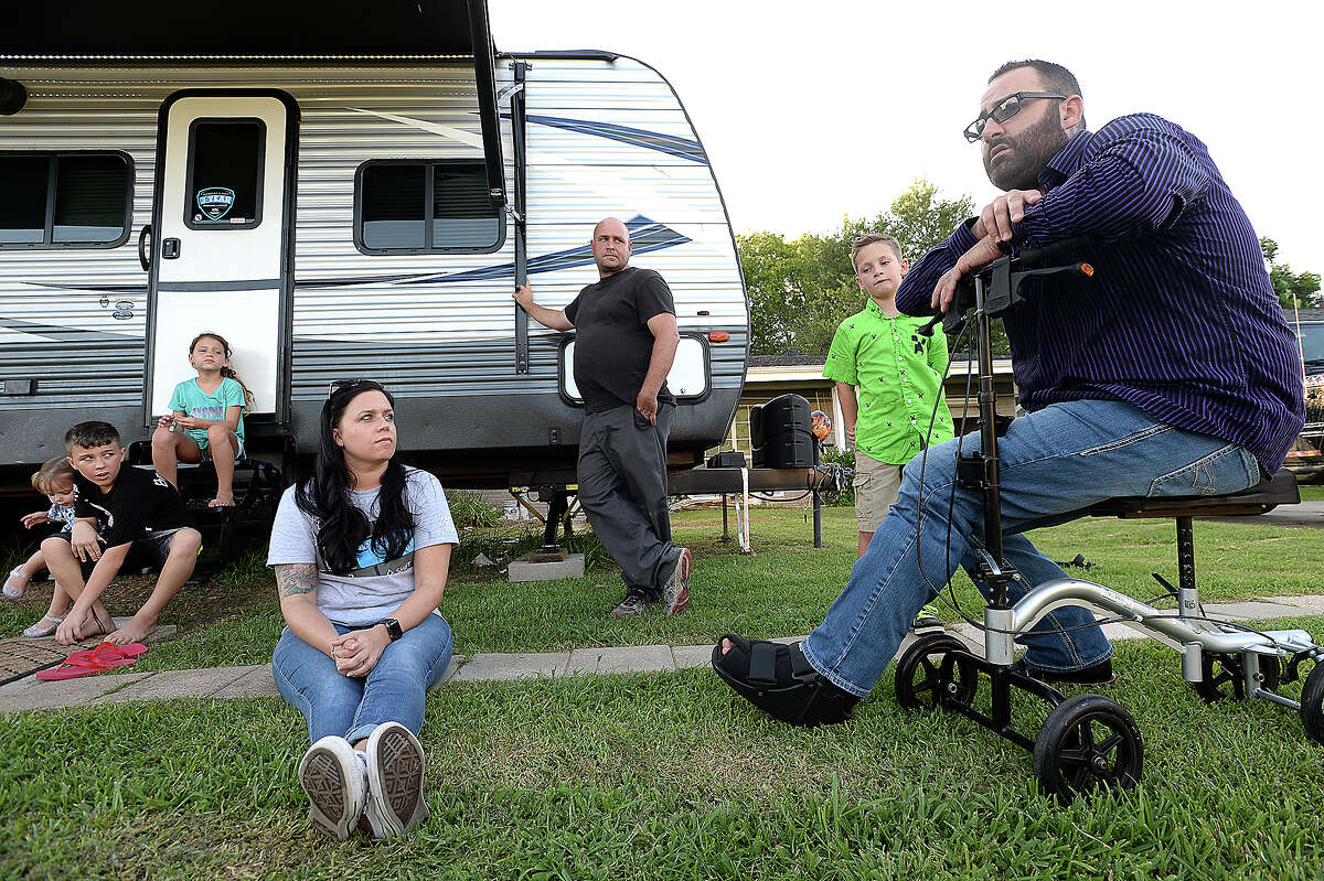 Keith Bass (right) talks with Amanda Skinner and Ray Cooper outside their trailer as they continue remodeling their flood-damaged home in Groves. Bass was part of the rescue efforts to help the family get to safety during Tropical Storm Harvey. Friday, August 17, 2018 Kim Brent/The Enterprise