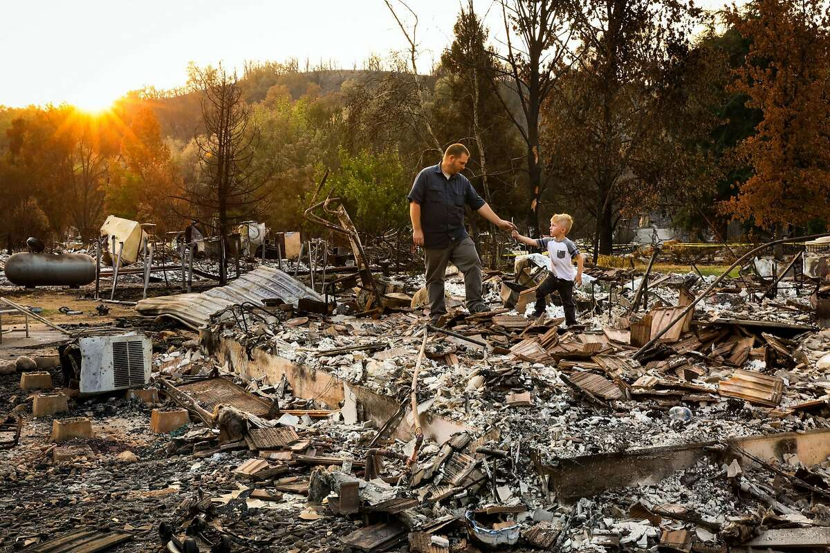 Daniel Wood, 5, (right) shows his grandfather Matthew Schjoth a wrench he found as they look through the destroyed remains of their home on Harlan Drive in Redding, California, on Thursday, Aug. 23, 2018.