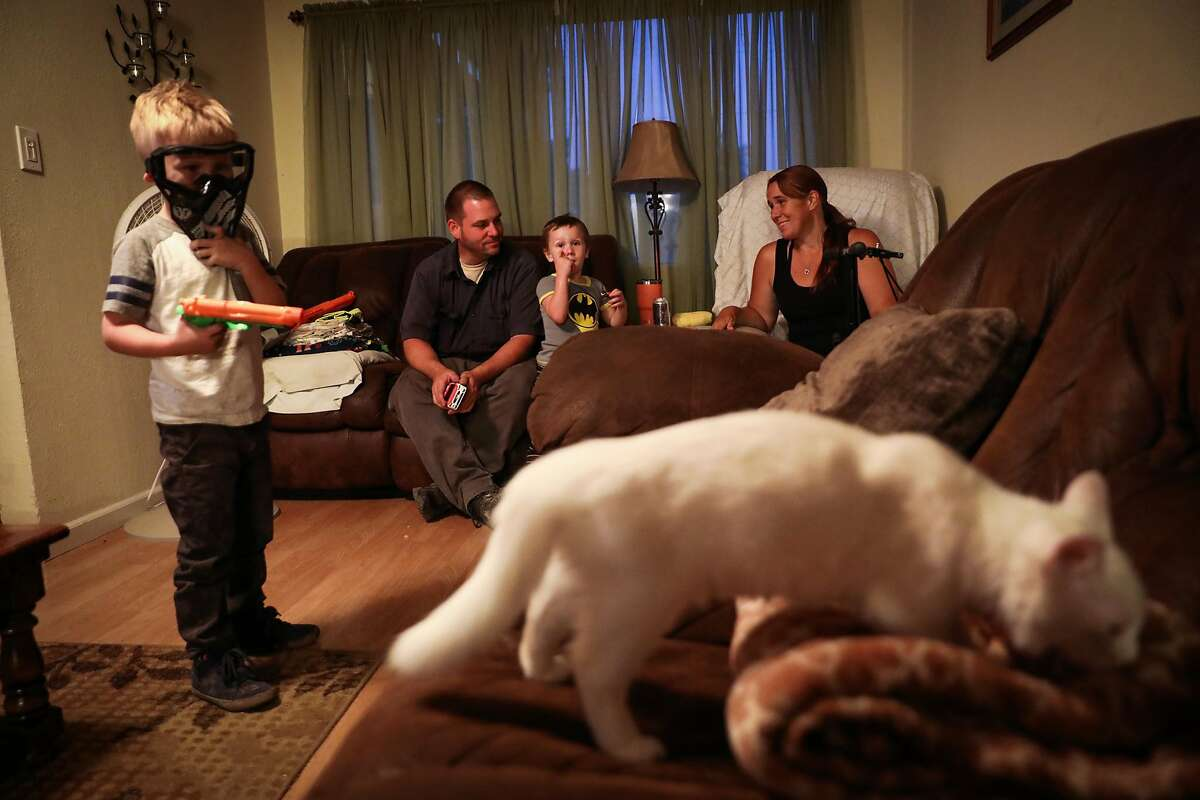 Matthew Schjoth (second from left) and his wife Kimberly Stevens (right) look after their grandsons Daniel Wood, 5 and Jacob Wood, 3 (center) while they stay with relatives in Redding, California, on Thursday, Aug. 23, 2018.