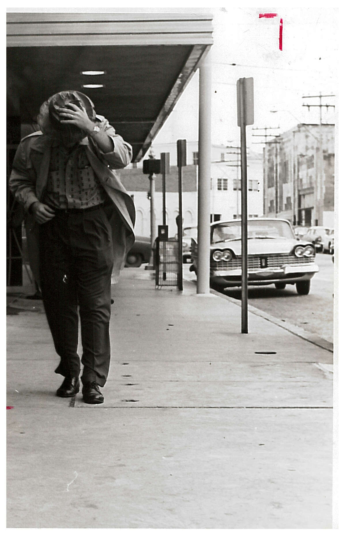 A man walks through gale winds in downtown Beaumont during Hurricane Carla. Photo taken September 1961 Enterprise archive photo