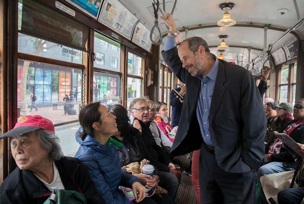 SFMTA Transit Chief Ed Reiskin chats with a passenger while riding a streetcar up Market Street from the SFMTA headquarters in San Francisco, Calif. Thursday, Aug. 23, 2018.