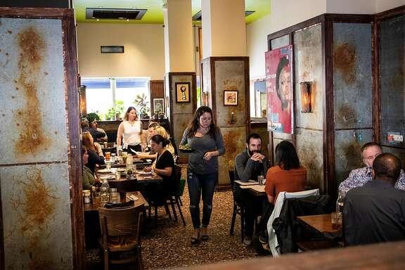 Erin Traylor, operation manager at Farmer Brown, center, carries a food order during dinner service�in San Francisco, Calif. on Wednesday, Aug. 22, 2018.