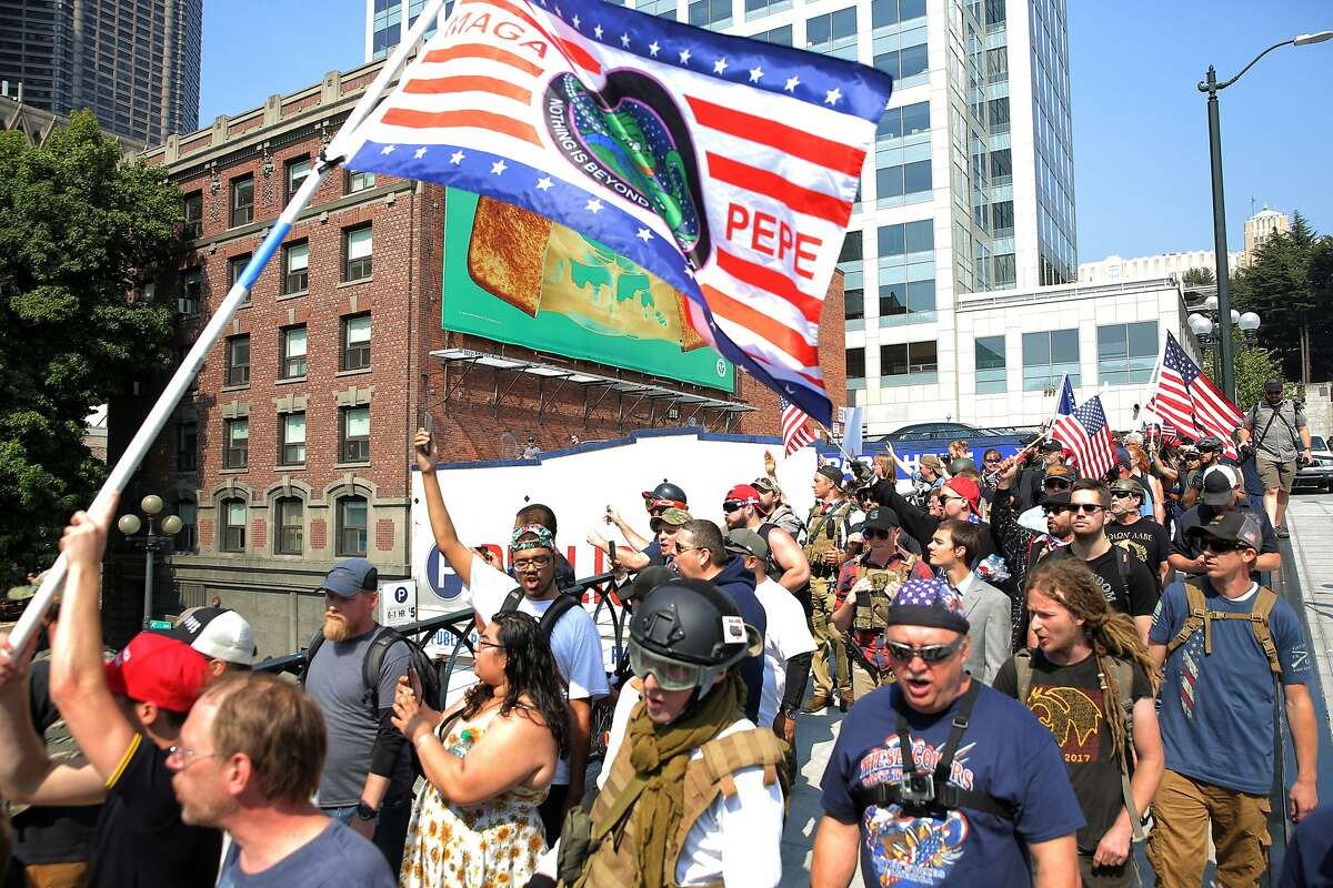 """Protesters from right-wing groups Washington 3 Percenters and Patriot Prayer march down Yesler Way during a """"Liberty or Death"""" rally at Seattle City Hall, in part, to oppose Washington gun-control Initiative 1639, Saturday, Aug. 18, 2018. Counter-protesters lined the other side of the street, at least two men were arrested. (Genna Martin, seattlepi.com)"""