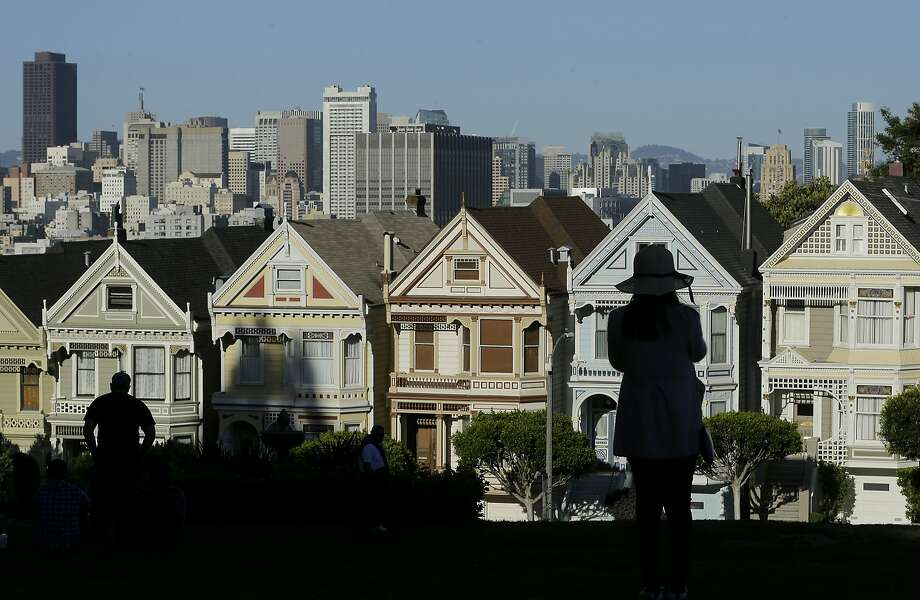 "FILE- In this April 15, 2016, file photo a woman looks toward the ""Painted Ladies,"" a row of historical Victorian homes, with the San Francisco skyline at rear at Alamo Square Park in San Francisco.  Photo: Jeff Chiu, Associated Press"