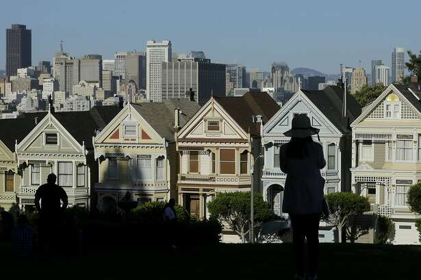"FILE- In this April 15, 2016, file photo a woman looks toward the ""Painted Ladies,"" a row of historical Victorian homes, with the San Francisco skyline at rear at Alamo Square Park in San Francisco. The Trump administration announced new rules Thursday, Aug. 23, 2018, aimed at preventing residents in high-tax states from avoiding a new cap on widely popular state and local tax deductions. (AP Photo/Jeff Chiu, File)"