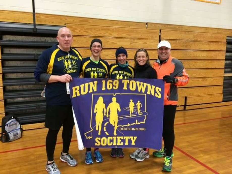 Fairfield's Mary Paglialunga, second from right, poses with other runners with the Run 169 Towns Society banner, a group created to compete in a road race in every town in Connecticut. Photo: Contributed Photo