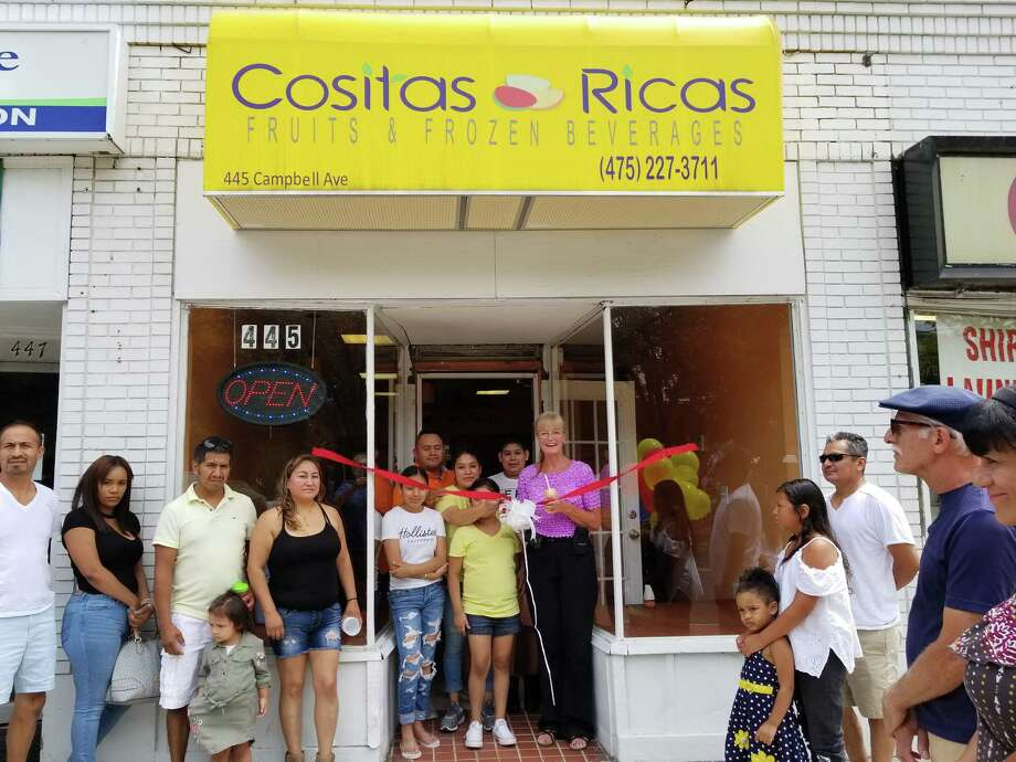 GRAB A BITE: West Haven Mayor Nancy R. Rossi, right, cuts the ribbon with Cositas Ricas owner Pilar Garcia Leon to celebrate the ceremonial opening of the fruit and frozen beverage shop at 445 Campbell Ave. Garcia is accompanied by her husband, Joan Cuapio, and her children, from left, Ashley Aguila Garcia, 14, Leslie Aguila Garcia, 9, and Francisco Aguila Garcia, 12. In a plaza across the street from the city Green, the new shop blends fresh fruits and fruit salads with creamy milkshakes and smoothies. Cositas Ricas also whips up authentic Latin American dishes, including quesadillas and tacos, along with sandwiches. Photo: Contributed Photo / Victor M. Borras - City Photo