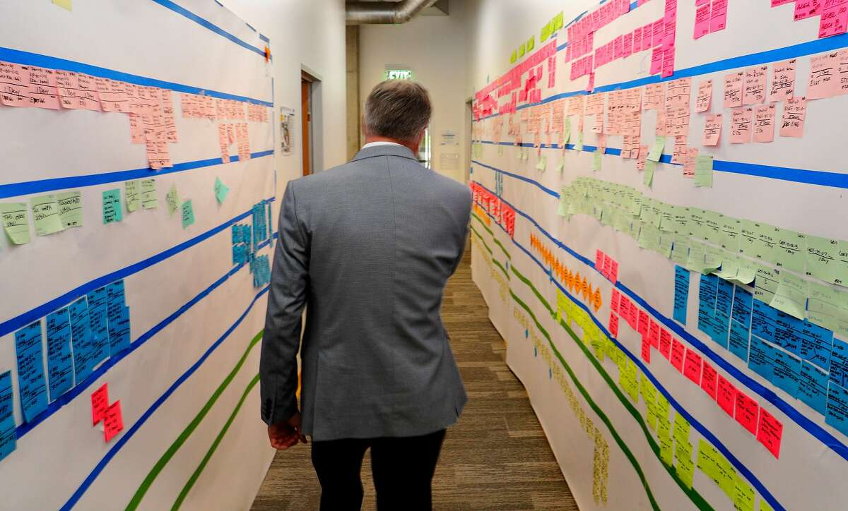 Warriors President and Chief Operating Officer Rick Welts walks by a past up progress board in the construction offices of the still-under-construction Chase Center in San Francisco, Calif., on Tuesday, August 21, 2018.