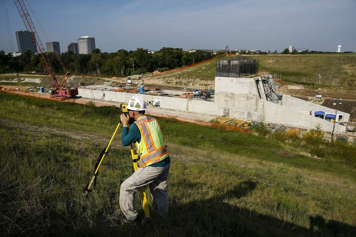 Granite Construction surveyor Johnathon McLoud stands on the cofferdam surrounding the construction of the new outlet works for Addicks Reservoir Thursday July 26, 2018 in Houston.