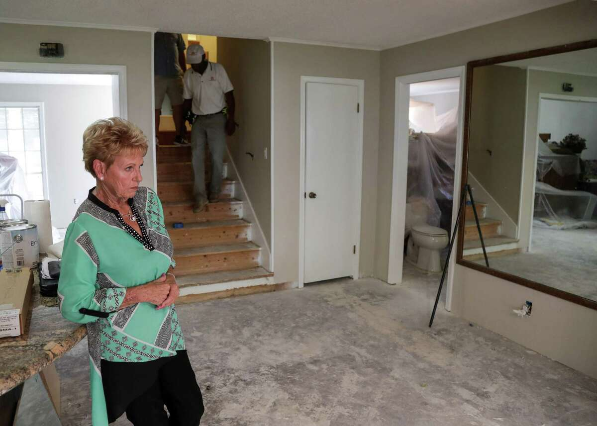 Martha Arvidsson waits in her home as her two new contractors, Homer Wilson and Jeremy Hawkins, in background, tour her home, Friday, Aug. 17, 2018, in Dickinson. Arvidsson hired a contractor after Hurricane Harvey, and she says he did shoddy work.