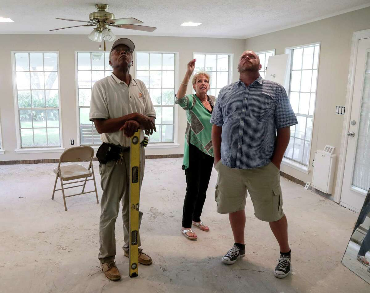 Arvidsson and her new contractors, Homer Wilson, left, and Jeremy Hawkins, examine the work of a previous contractor.